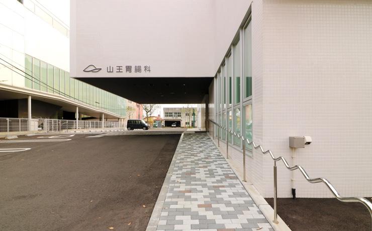 裏通りから病院を眺めた図。駐車場を完備しています。